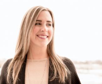 Kelly Nash smiling in black poncho sweater