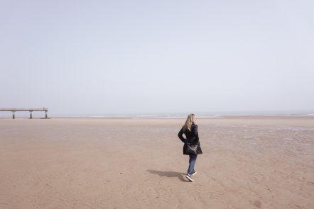 Kelly walks along Omaha Beach in Normandy, France as the sun peeks out.