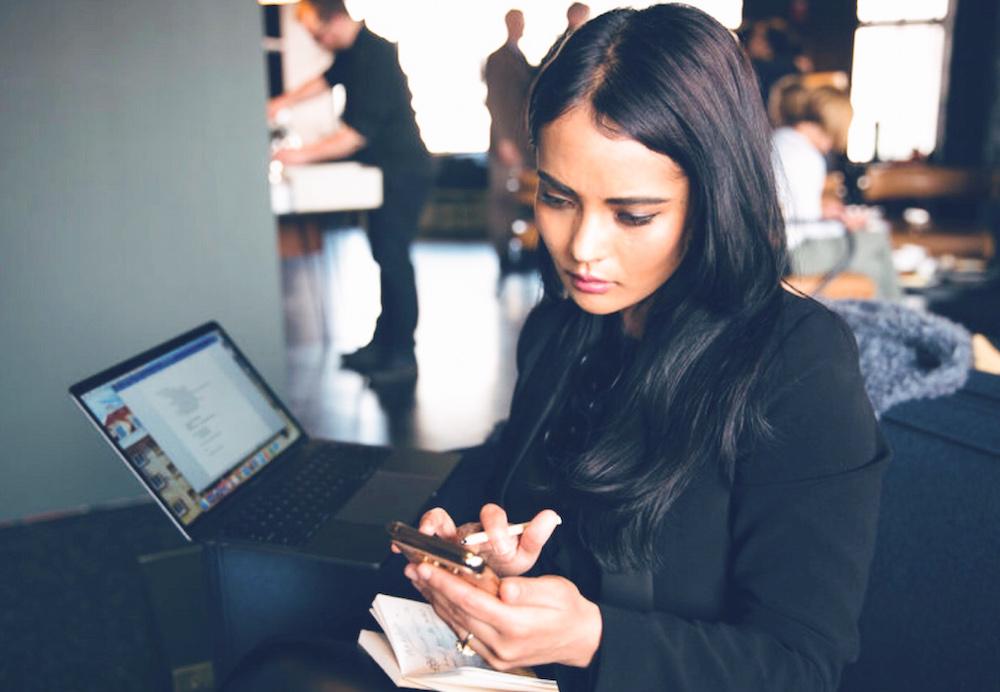 Megha Hamal works on her phone.