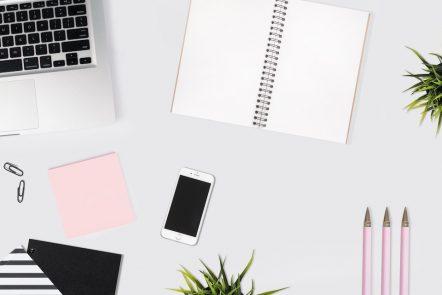Notebook, computer, notebokok and a pen lay on a desk.